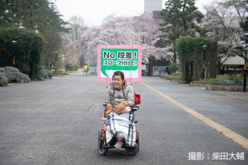 女性の車椅子のパレードの参加者が車椅子の後ろに「No、段差!スロープつけて!」と書いたプラカードをつけて笑顔で微笑んでいる。