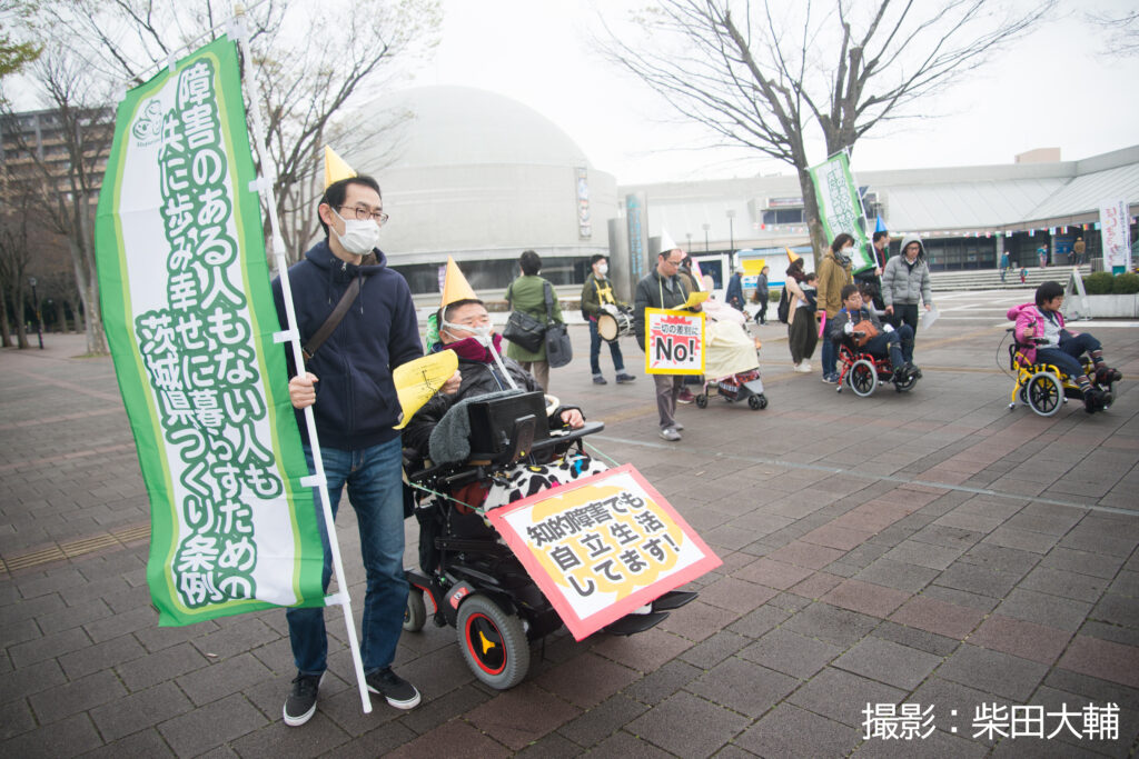 車椅子の参加者はプラカードを後ろにつけて、その介助の参加者は条例の上り旗を手に持ち、パレードしている様子