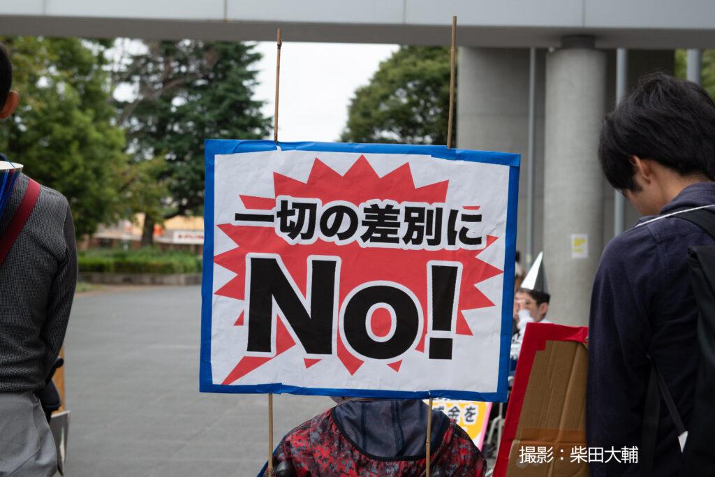 パレードで車椅子の男性が背中に「一切の差別にNo!」と書いたブラカードをつけている
