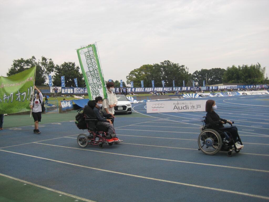 車椅子の人がグラウンドを周回している様子